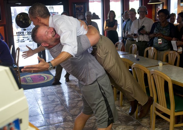 US President Barack Obama is picked up by Scott Van Duzer, owner of Big Apple Pizza and Pasta Italian Restaurant during a visit to the restaurant in Fort Pierce, Florida, September 9, 2012, during the second day of a 2-day bus tour across Florida. (Photo by Saul Loeb/AFP Photo)