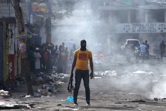 A man holds a weapon next to burning barricades during anti-government protests in Port-au-Prince, February 17, 2019. (Photo by Ivan Alvarado/Reuters)