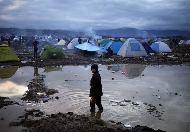 A migrant boy stands in a puddle in a makeshift camp on the Greek-Macedonian border, near the village of Idomeni, Greece March 10, 2016. (Photo by Stoyan Nenov/Reuters)