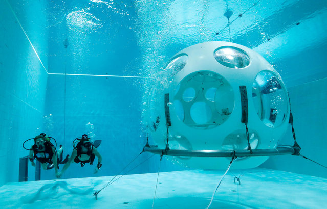 """Belgians Florence Lutje Spelberg and Nicolas Mouchart dive next to """"The Pearl"""", a spheric dining room placed 5 metres underwater in the NEMO33 diving center, one of the world's deepest pools (33 metre/36 yards) built to train professional divers, before enjoying a meal inside, in Brussels, Belgium January 30, 2017. (Photo by Yves Herman/Reuters)"""