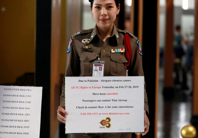 A police officer holds a placard with information after Thai Airway cancelled all the flights to and from Europe at Suvarnabhumi Airport in Bangkok, Thailand on February 28, 2019. (Photo by Soe Zeya Tun/Reuters)