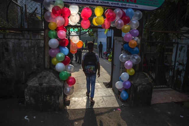 A student walks in through an entrance decorated with balloons during the partial reopening of a school that remained closed due to the coronavirus pandemic at Dharavi, one of Asia's largest slums, in Mumbai, India, Monday, October 4, 2021. (Photo by Rafiq Maqbool/AP Photo)