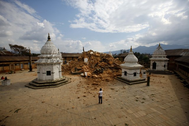 People look at the debris of one of the oldest temples after it was damaged in Saturday's earthquake, in Kathmandu, Nepal, Sunday, April 26, 2015. (Photo by Niranjan Shrestha/AP Photo)