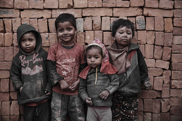 A group of dust covered child labourers gather for a portrait in the brick kiln in Kathmandu Valley, Nepal, 22 February 2015. Bleak photos identify the children working their fingers to the bone in Nepalís brick kilns. Photographer Jan Mˆller Hansen documented the conditions of the brick kilns in Kathmandu Valley, Nepal between 2013 and 2016 while he lived and worked in the area. Jan estimates between 150,000 and 175,000 people are employed in the 200 brick kilns littering the Kathmandu Valley. (Photo by Jan Moeller Hansen/Barcroft Images)