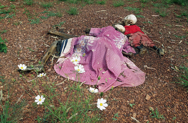 In this May 31, 1994, file photo, the bodies of a woman and her child lie by a church in Nyarubuye parish, which was the site of an April 14 massacre that survivors say was perpetrated by a militia assisted by government gendarmes, about 95 miles east of the capital Kigali, in Rwanda. The scale of the 1994 killings was massive and the reporting and photographs taken at the time helped inform the world of the horrors of the genocide. (Photo by Jean-Marc Bouju/AP Photo/File)