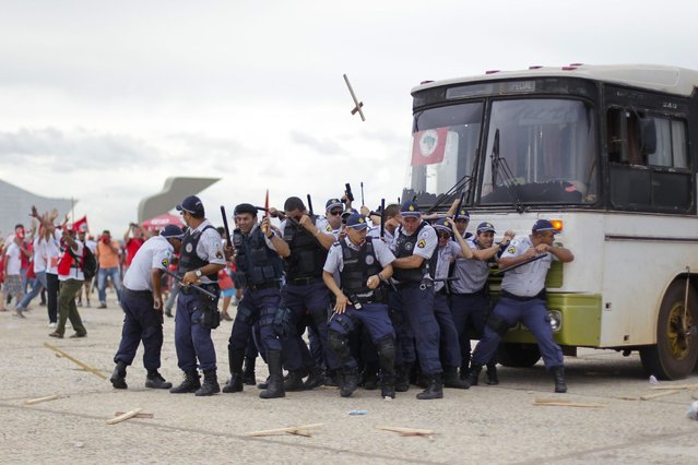 Military policemen take cover during a clash with members of the Landless Workers Movement (MST) at a demonstration in Brasilia February 12 , 2014. (Photo by Ueslei Marcelino/Reuters)