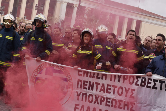 Smoke from flares rises around firefighters chanting slogans during a rally in central Athens to protest hiring conditions on February 8, 2017. Hundreds of contract firefighters from all over Greece staged the protest to demand long- promised staff positions. (Photo by Louisa Gouliamaki/AFP Photo)
