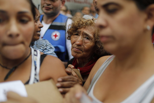In this April 16, 2019 photo, people wait to be given empty water containers and water purification pills during the first aid shipment from the Red Cross in Caracas, Venezuela. In late March, the Red Cross federation announced it would soon begin delivering assistance to an estimated 650,000 people and vowed that it would not accept interference from either side of the polarized country. (Photo by Ariana Cubillos/AP Photo)