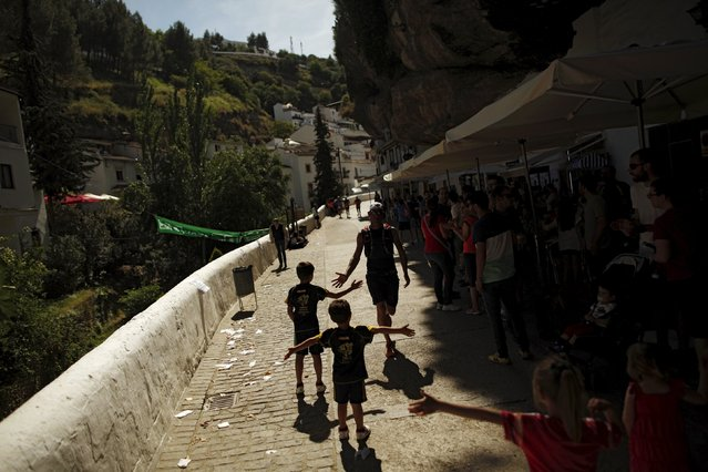 A runner shakes hands with children as he participates in the XVIII 101km international competition in Setenil de las Bodegas, southern Spain, May 9, 2015. (Photo by Jon Nazca/Reuters)
