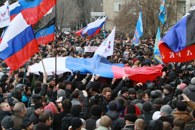 Pro-Russian activists hold Russian flags during a rally in the center of Donetsk, Ukraine, Saturday, March 1, 2014. (Photo by Sergey Vaganov/AP Photo)