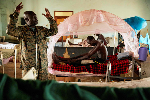 A South Sudan People's Defence Force (SSPDF) chaplain prays during a visiting to soldier at Juba Military Hospital in Juba, South Sudan, on April 27, 2019. Despite a ceasefire arrangement signed by the government and the opposition forces last year, violence or inter-ethnic fights have continued within the country. A peace deal signed in September 2018 by the parties of the country's six-year-old conflict calls for the formation of a government of national unity on May 12. (Photo by Alex McBride/AFP Photo)