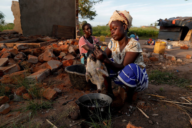 """Maria Jofresse, 25, watches her mother Ester Thoma preparing food beside their damaged house in the aftermath of Cyclone Idai, in the village of Cheia, which means """"Flood"""" in Portuguese, near Beira, Mozambique April 4, 2019. (Photo by Zohra Bensemra/Reuters)"""