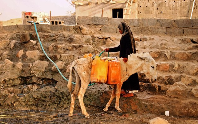 A displaced Yemeni woman from Hodeida fills water containers at a make-shift camp in a village in the northern district of Abs in the country's Hajjah province, on May 9, 2019. The Yemeni conflict has triggered what the United Nations describes as the world's worst humanitarian crisis, with 3.3 million people still displaced and 24.1 million in need of aid. (Photo by Essa Ahmed/AFP Photo)