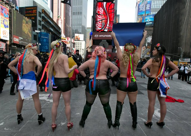 Female activist members of FEMEN go topless during their anti-Putin, pro-Ukraine demonstration in New York's Times Square, Thursday, March 6, 2014. (Photo by Richard Drew/AP Photo)