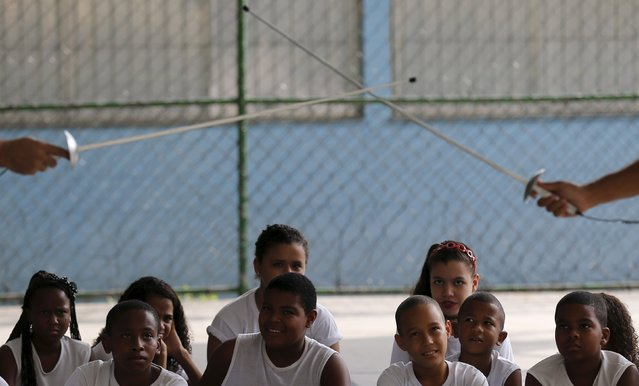 """Children from municipal school Parana watch fencing instructors during the project """"Fencing School"""" in Rio de Janeiro, Brazil, March 30, 2016. (Photo by Sergio Moraes/Reuters)"""