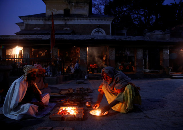 Hindu holy men, or sadhus, sit beside a fire at the premises of Pashupatinath Temple, ahead of the Shivaratri festival, in Kathmandu, Nepal February 20, 2017. (Photo by Navesh Chitrakar/Reuters)
