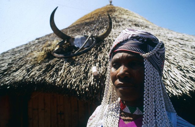 Pictured here is a female Sangoma with a dried and decorated goat bladder on her head. Finding a hidden goat, killing it and using its bladder as a hat is supposed to help a future Sangoma communicate better with the spirits of his or her ancestors during the graduation test and throughout the rest of their lives. (Photo by Patrick Durand/Sygma via Getty Images)