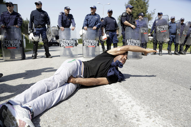 A migrant gestures as he lies on a ground after a scuffle with police, during road blockade at the northern Greek border point of Idomeni, Greece, Monday, April 4, 2016. A plan to send back migrants from Greece to Turkey sparked demonstrations by local residents in both countries  days before the deal brokered by the European Union is set to be implemented. (Photo by Amel Emric/AP Photo)