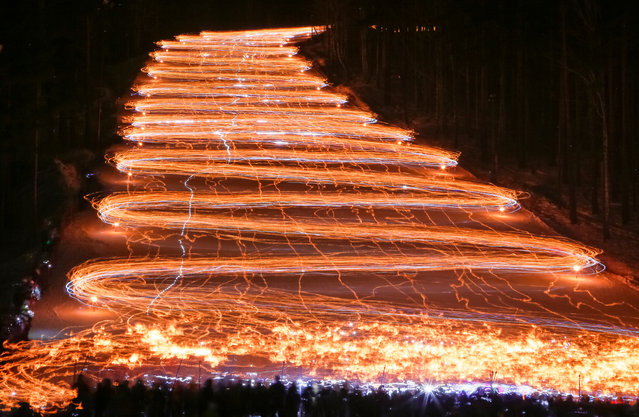 Hundreds of skiers and snowboarders descend from a slope while holding lit torches and flashlights in the Siberian town of Zheleznogorsk, northeast of Krasnoyarsk, Russia, February 26, 2017. (Photo by Ilya Naymushin/Reuters)
