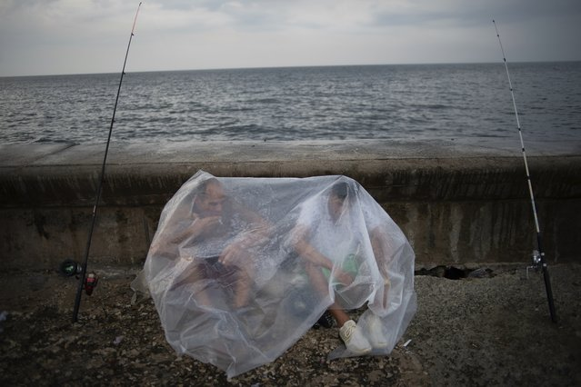 Engelbert Cañete, left, and his friend Ethian Jesus, sit protected by a plastic tarp as they wait out the rain to resume fishing from the Malecon, or seawall, in Havana, Cuba, Monday, May 6, 2019. (Photo by Ramon Espinosa/AP Photo)
