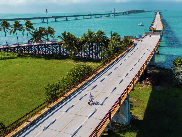 The Overseas Highway makes its seven-mile journey across acqua tinted waters and over Pigeon Key, an island that housed the workers that built this landmark railroad once coined the Eighth Wonder of the World. (Photo by Chase Guttman/Caters News)