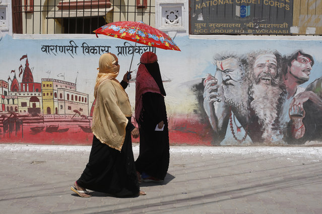 Indian Muslims women on way to a polling station to cast their votes walk past a mural showing Hindu holy men during the seventh and final phase of national elections in Varanasi, India, Sunday, May 19, 2019. Indians are voting in the seventh and final phase of national elections, wrapping up a 6-week-long long, grueling campaign season with Prime Minister Narendra Modi's Hindu nationalist party seeking reelection for another five years. Counting of votes is scheduled for May 23. (Photo by Rajesh Kumar Singh/AP Photo)