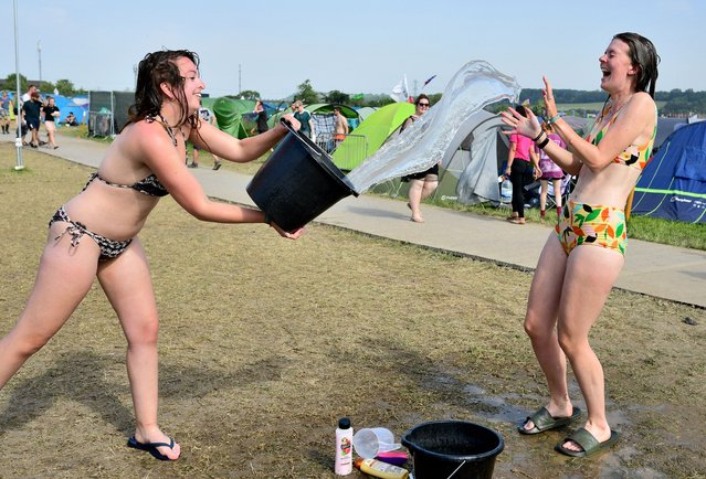 Festival-goers wearing bikinis pour buckets of water over each other during day four of Glastonbury Festival at Worthy Farm, Pilton on June 29, 2019 in Glastonbury, England. Glastonbury is the largest greenfield festival in the world, and is attended by around 175,000 people. (Photo by Leon Neal/Getty Images)