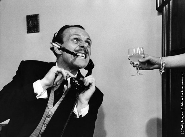 1954: English actor-comedian Terry Thomas, real name Thomas Terry Hoar-Stevens, demonstrates how an exhausted husband slaves late into the night, to keep his wife in idleness and luxury