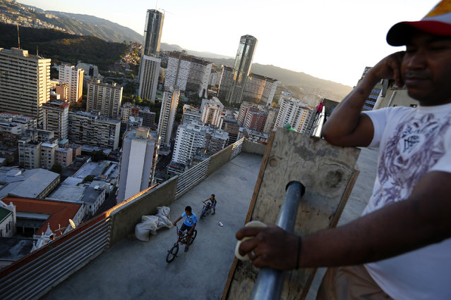 """Children ride bicycles on one of the top inhabited floors of the """"Tower of David"""" skyscraper in Caracas February 9, 2014. (Photo by Jorge Silva/Reuters)"""