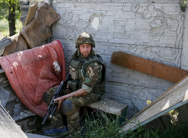 """A member of the Ukrainian armed forces is seen in the town of Maryinka, eastern Ukraine, June 5, 2015. Ukraine's president told his military on Thursday to prepare for a possible """"full-scale invasion"""" by Russia all along their joint border, a day after the worst fighting with Russian-backed separatists in months.  REUTERS/Gleb Garanich"""