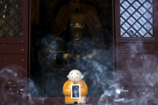 Robot Xian'er is seen behind smoke from burning incense after it was placed in the main building of Longquan Buddhist temple for photograph by the temple's staff, on the outskirts of Beijing, April 20, 2016. (Photo by Kim Kyung-Hoon/Reuters)