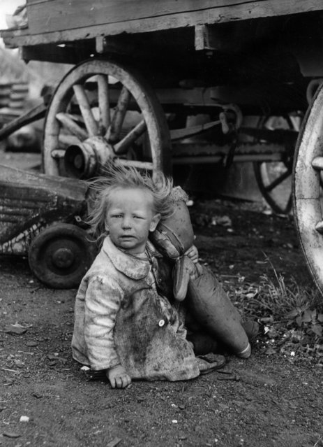A little gypsy girl sits by the wheel of a caravan clutching a doll, 28th July 1951. Her clothes are filthy and her face dirty. She is one of the three hundred squatters at Corke's Meadow, Kent. The group includes true gypsies, mumpers, posh-rats and hobos. (Photo by Bert Hardy/Picture Post/Getty Images)
