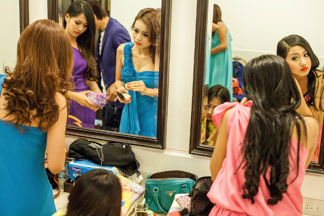 Professional models from the Sun Model Agency put the finishing touches to their look backstage before modelling in a show at the Sofitel Hotel on March 30, 2014 in Phnom Penh, Cambodia. (Photo by Omar Havana/Getty Images)