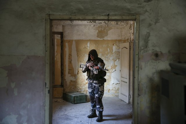"""Leonid, """"Kartoris"""", 28, wears a stalker costume which identifies the group """"Monolith"""", as he poses for a portrait in Moscow, Russia, March 26, 2016. A game known as S.T.A.L.K.E.R., named after a popular computer shooter, is fast winning the minds of intellectuals across the former Soviet Union who take on roles of mutants, zombies and warriors on unfinished construction sites. As the 30th anniversary of the nuclear disaster in Chernobyl is marked on April 26, enacting a post-apocalyptic world is a philosophy that warns of the perils of uncontrolled use of nuclear power, the game's enthusiasts claim. (Photo by Maxim Shemetov/Reuters)"""
