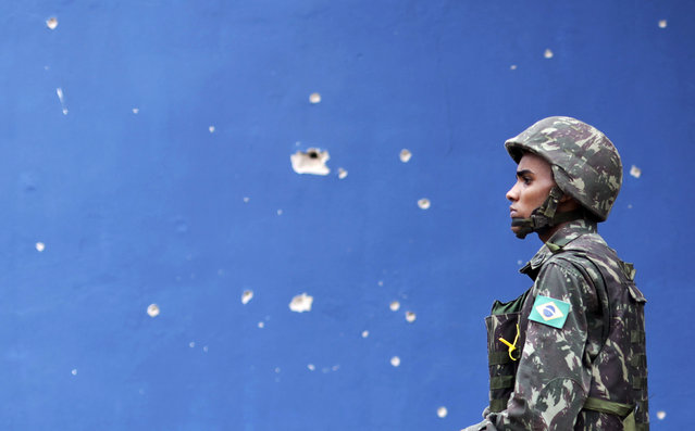 A Brazilian Army soldier walks past bullet holes in a wall during an operation in the Mare slums complex in Rio de Janeiro March 26, 2014. (Photo by Ricardo Moraes/Reuters)