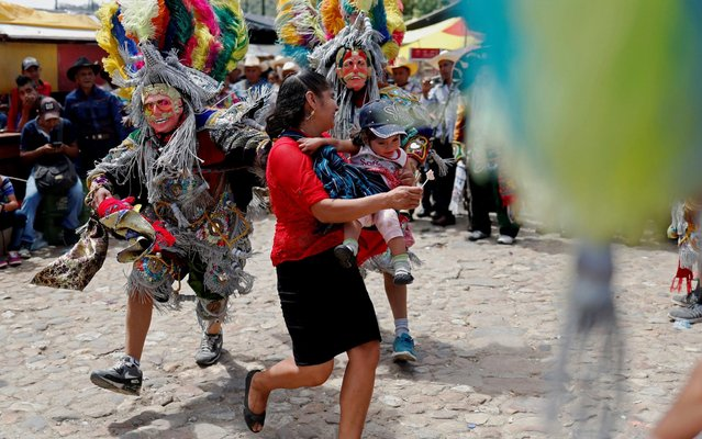 Dancers scare a woman and her child during the Cubulco Fair in Baja Verapaz, Guatemala, 25 July 2019. The indigenous municipality of Cubulco holds its fair annually to celebrate Saint James the Great. (Photo by Esteban Biba/EPA/EFE/Rex Features/Shutterstock)