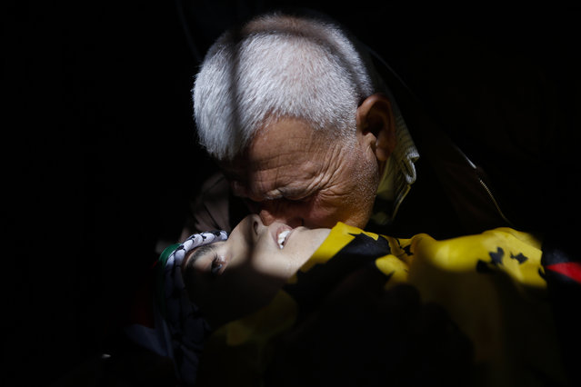 """A relative kisses the body of a 17-year old Palestinian Mahmoud Hattab during his funeral at the Jalazoun refugee camp near the West Bank city of Ramallah, Friday, March 24, 2017. The Palestinian Health Ministry said Israeli troops killed the 17-year-old Palestinian and wounded another three when soldiers opened fire on their car in the West Bank. The Israeli military said the men had exited their vehicle near a Jewish settlement and """"hurled fire bombs"""" at the community. It said the soldiers fired at the attackers, who fled the scene in their vehicle. (Photo by Majdi Mohammed/AP Photo)"""