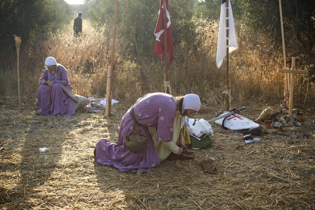 In this Friday, July 3, 2015 photo, Israeli and Russian members of knight clubs get dressed early morning before marching 27 kilometers (17 miles) to the reenactment of the Battle of Hattin from the ancient northern city of Zippori to Horns of Hattin, northern Israel. (Photo by Oded Balilty/AP Photo)