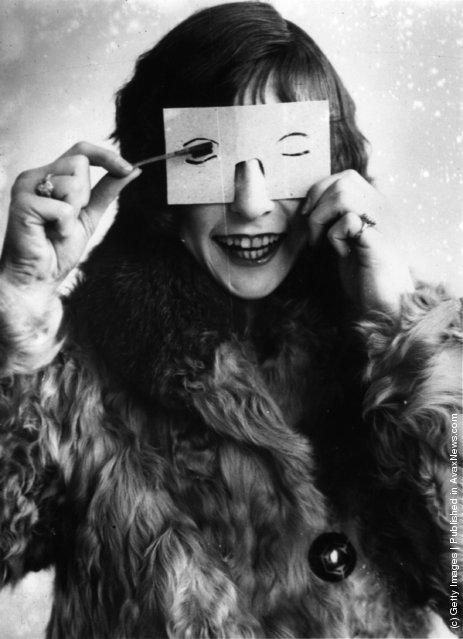 A woman applying make-up using an eyelash stencil, 1926