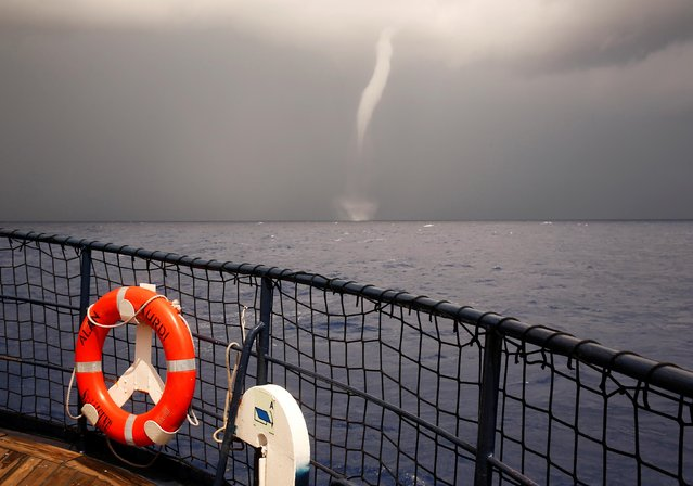 """A waterspout is seen from the German NGO Sea-Eye migrant rescue ship """"Alan Kurdi"""" as it waits for further instructions after rescuing Tunisian migrants, in international waters off Malta in the central Mediterranean Sea, September 4, 2019. (Photo by Darrin Zammit Lupi/Reuters)"""