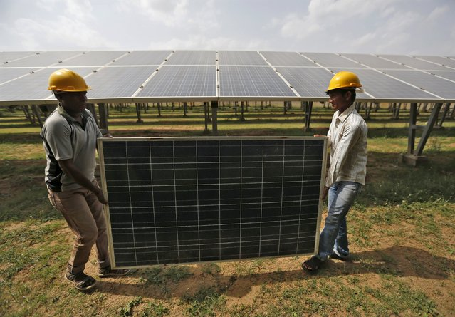 Workers carry a damaged photovoltaic panel inside a solar power plant in Gujarat, India, July 2, 2015. India's $100 billion push into solar energy over the next decade will be driven by foreign players as uncompetitive local manufacturers fall by the wayside, no longer protected by government restrictions on the sector. (Photo by Amit Dave/Reuters)