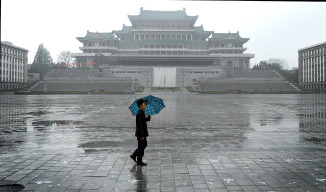 A man walks by the Grand People's Study House in Pyongyang, North Korea on May 6, 2016. The central library was constructed in a traditional Korean style in April 1982 over a period of 21 months to celebrate leader Kim Il-sung's 70th birthday. (Photo by Linda Davidson/The Washington Post)