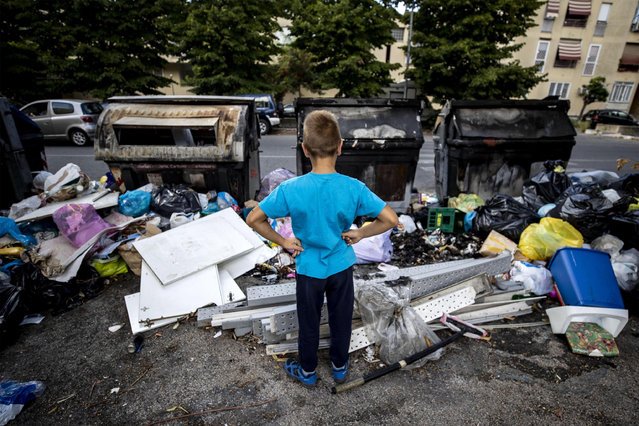 A kid looks at the garbage that occupies the sidewalk in the Quartaccio suburb, Rome, Italy, 10 September 2019. The closure for maintenance work of some waste-treatment plants created last week new difficulties to the deal with treatment of urban garbage in Rome. (Photo by Massimo Percossi/EPA/EFE)
