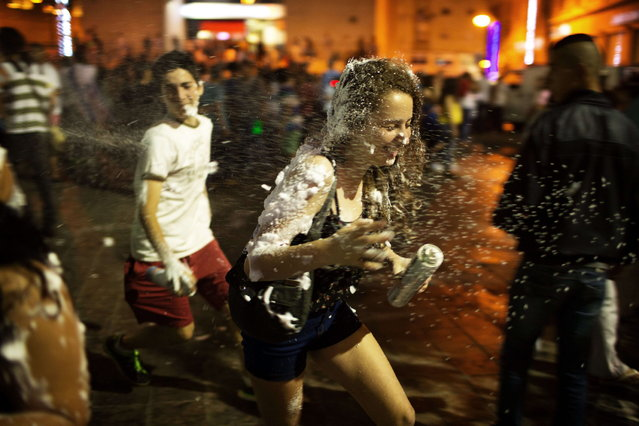 Israelis  sprays foam as they celebrate at the center of Jerusalem, on May 5, 2014, the Israel's 66th anniversary the Independence Day celebrations. Israel's first Prime Minister David Ben-Gurion declared the existence of the State of Israel in Tel Aviv in 1948, ending the British mandate. (Photo by Menahem Kahana/AFP Photo)