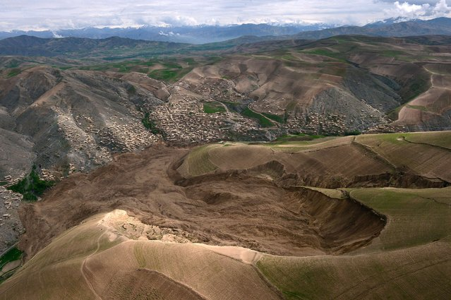 The mud and rocks of the landslide are pictured in this aerial view of Aab Bareek village at Argo district in Badakhshan province on May 5, 2014. Afghan officials said they plan to build new houses for hundreds of families made homeless by a landslide that entombed a northeastern village and killed at least 300 people. (Photo by Wakil Kohsar/AFP Photo)
