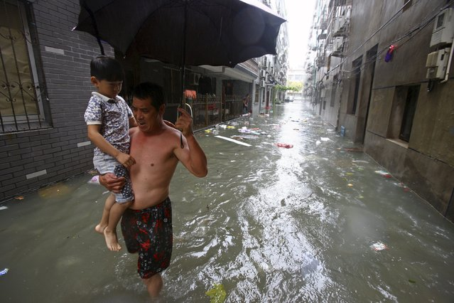 A man holds his grandson as he walks along a flooded street amid heavy rainfall under the influence of Typhoon Chan-hom, in Ningbo, Zhejiang province, China, July 11, 2015. (Photo by Reuters/Stringer)