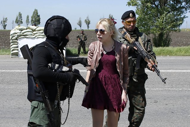 A woman is led aside as her partner is detained by Ukrainian security forces for being aggressive at an army checkpoint in the southeastern port city of Mariupol, on May 11, 2014. Residents' attitudes appear to have hardened considerably with the deaths of dozens of pro-Russian activists in the city of Odessa this month and with reports that troops fired at a crowd in Mariupol last week. (Photo by Marko Djurica/Reuters)