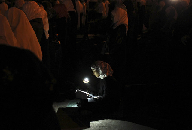A woman uses her mobile phone to illuminate the Koran as supporters of the Jordanian opposition and Syrians living in Jordan perform prayers during the holy month of Ramadan before a protest in front of the Syrian Embassy in Amman August 2, 2011. (Photo by Muhammad Hamed/Reuters)