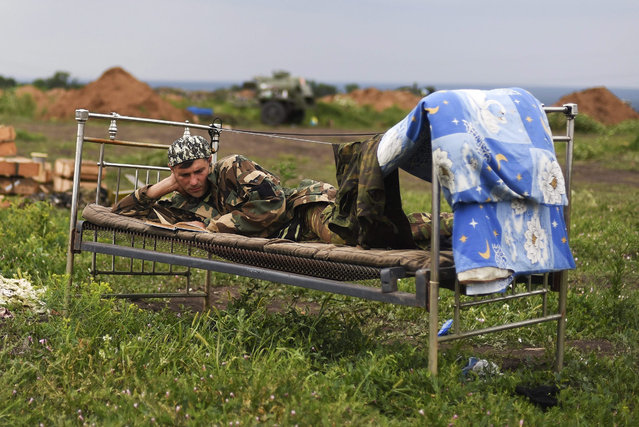 A Ukrainian serviceman of the volunteers battalion Kyiv-2 reads a book at their position near Krymske village of Lugansk area, Ukraine, 14 July 2015. The conflict in Ukraine is taking an increasing toll on its citizens with nearly one in nine people needing humanitarian assistance, the UN emergency aid office said 10 July, in Geneva. (Photo by Ivan Boberskyy/EPA)