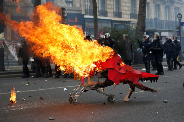 Flames from a burning cardboard dragon in a caddy are seen near French CRS riot police during clashes as part of the traditional May Day labour union march in Paris on May 1, 2017. (Photo by Gonzalo Fuentes/Reuters)